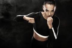 Um atlético forte, pugilista da mulher, encaixotando no treinamento no fundo preto Conceito do encaixotamento do esporte com espa imagens de stock