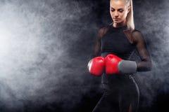 Um atlético forte, pugilista da mulher, encaixotando no treinamento no fundo preto Conceito do encaixotamento do esporte com espa fotos de stock royalty free