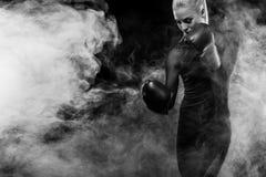 Um atlético forte, pugilista da mulher, encaixotando no treinamento no fundo preto Conceito do encaixotamento do esporte com espa foto de stock
