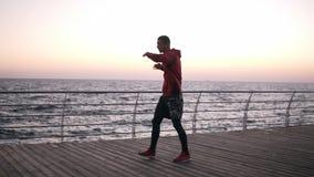 Um atleta aquece-se durante um exercício do amanhecer contratado no encaixotamento O homem caucasiano que exercita, faz o torso g vídeos de arquivo
