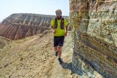 Um atleta do homem corre através das montanhas do deserto imagem de stock