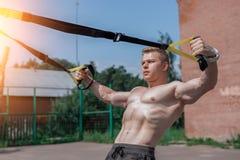 Um atleta masculino é contratado em laços do ar livre, treina para trás, prendendo No verão, no short e em um torso desencapado E Fotografia de Stock