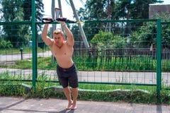 Um atleta masculino é contratado no laço do ar livre, treina o tríceps na cerca No verão, no short e em um torso desencapado Saud Fotos de Stock Royalty Free