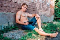 Um atleta masculino moderno no short está sentando-se na rua com uma tabuleta e os fones de ouvido, olhando um filme em redes soc Imagens de Stock
