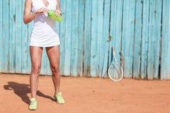 Um atleta novo está guardando uma garrafa da água em suas mãos imagem de stock