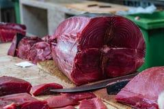 Um atum que está sendo limpado e cortado em um mercado de peixes imagem de stock royalty free