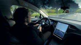 Um automóvel automático está movendo-se ao longo da estrada com seu motorista que senta-se para dentro video estoque