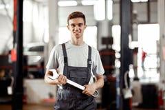 Um automechanic bonito está estando em um serviço de reparações do carro com uma chave em sua mão foto de stock