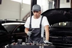 Um automechanic novo é centrado sobre o processo de reparar um carro imagens de stock