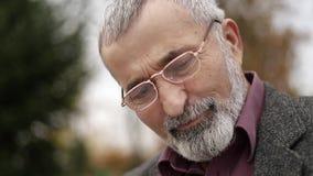 Um avô agradável com uma barba bonita em um revestimento cinzento senta-se em um banco no parque e lê-se um jornal vídeos de arquivo