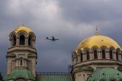 Um avião voa entre as abóbadas de uma igreja na perspectiva de um céu dramático Fotografia de Stock Royalty Free