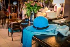 Um azul largo-brimmed o chapéu do ` s da senhora e um lenço feito a mão imagem de stock