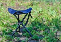 Um azul que dobra a cadeira alta para acampar em uma clareira do verde do verão Fotos de Stock Royalty Free