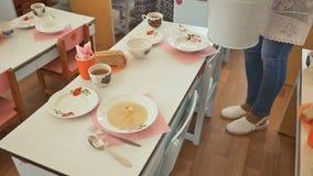 Um baby-sitter derrama a sopa para crianças prées-escolar Preparação para o almoço no jardim de infância O jardim de infância do  video estoque