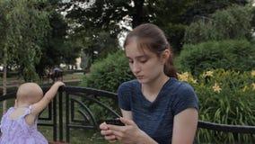 Um baby-sitter muito novo que joga um jogo em seu smartphone Um fim da posição do bebê perto com ela de volta à câmera video estoque