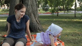 Um baby-sitter novo que põe um bebê para baixo sobre uma cobertura O bebê rasteja afastado video estoque