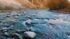 Um baixo voo sobre uma cachoeira pequena e um rio da montanha, e pedras de cristal de turquesa entre as montanhas No arquivo de filme