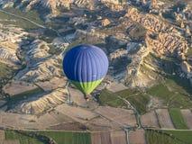 Um balão voa sobre o parque nacional de Goreme fotografia de stock