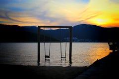 Um balanço no mar com o por do sol surpreendente foto de stock royalty free