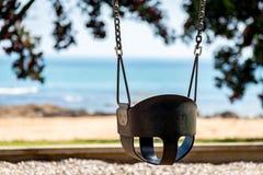 Um balanço vazio em um campo de jogos pelo mar fotografia de stock