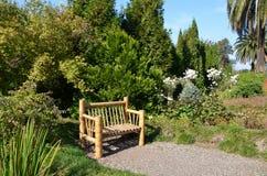 Um banco de bambu no jardim imagens de stock royalty free