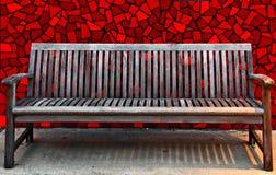 Um banco de madeira com a parede vermelha da telha Foto de Stock Royalty Free