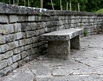 Um banco de pedra robusto colocado contra uma parede de tijolo de pedra Jardim bot?nico de Visby em Gotland, Su?cia imagens de stock royalty free