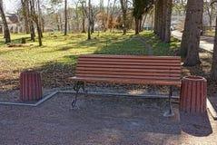 Um banco marrom no parque e em uma urna Imagens de Stock
