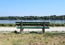 Um banco pelo rio imagem de stock