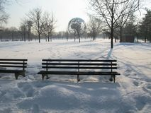Um banco vazio coberto pela neve imagem de stock