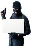 Um bandido armado perigoso que guarda um cartaz da inscrição Imagem de Stock