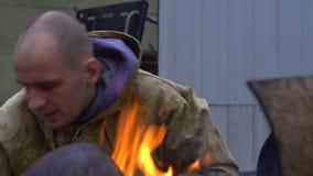 Um bandido puxa uma faca perto do fogo vídeos de arquivo