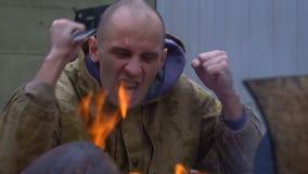 Um bandido puxa uma faca perto do fogo filme
