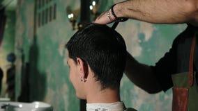 Um barbeiro penteia delicadamente o cabelo úmido curto do cliente masculino Barbeiro farpado no avental que penteia o cabelo de u filme