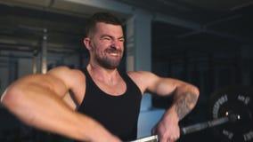 Um barbell de levantamento do homem considerável Barra pesada do gym da aptidão de Crossfit pelo exercício forte filme