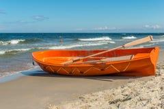 Um barco alaranjado da emergência na praia bonita imagens de stock