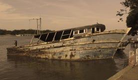 Um barco danificado do pescador em um porto pequeno indiano fotografia de stock