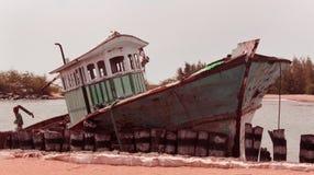 Um barco danificado e arruinado do pescador em um porto pequeno indiano fotografia de stock royalty free
