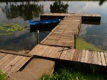 Um barco de madeira azul perto do cais velho, árvores viradas é refletido na superfície da lagoa Imagem de Stock