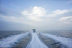 Um barco de motor branco apressa-se através do mar azul, saindo de uma fuga imagens de stock