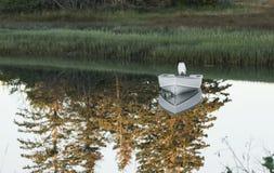 Um barco de motor pequeno em um lago com as árvores que refletem na água Imagens de Stock