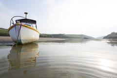 Um barco de navigação pequeno que senta-se no banco da areia do rio Gannel, em Cornualha fotos de stock royalty free
