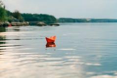 Um barco de papel navega pelo rio no verão Tem uma cor alaranjada e flutuadores rio abaixo ao longo da costa fotos de stock royalty free