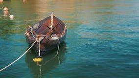 Um barco de pesca ? amarrado na costa Lentamente balan?ando em uma onda em um dia de ver?o claro video estoque