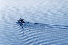 Um barco de pesca azul que viaja para fora no mar Fotos de Stock