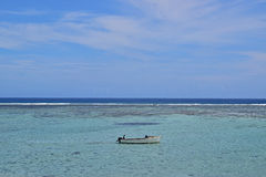 Um barco de pesca de madeira pequeno com dois pescadores em um seaview com horizonte que separa a água e o céu Fotos de Stock Royalty Free
