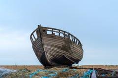 Um barco de pesca destruído saiu para deteriorar na praia imagens de stock royalty free