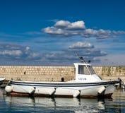 Um barco de pesca de madeira em um porto pequeno imagem de stock