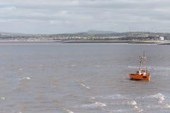 Um barco de pesca pequeno pequeno é balançado pelas ondas e pelo tempo ventoso na baía de Morecambe - inverno 2019 foto de stock royalty free
