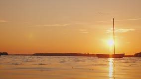 Um barco de pesca só na superfície do espelho do lago O sol de ajuste ilumina tudo com luz alaranjada filme